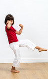 excited child showing her strength, enjoying exercising fun martial art - 223390949