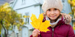 childhood, season and real estate concept - close up of happy little girl with fallen maple leaf in autumn over living house background outdoors