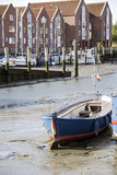 stranded wooden boat on the mudflat at low tide in the port of husum in germany, vertical, selected focus - 223398557