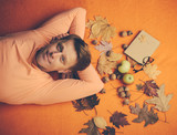 Red-haired man lies on an orange background. Autumn mood and the weather are warm and sunny and rain is possible. Top view. - 223398984