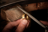 goldsmith hand holds a golden ring on the wooden workbench and works on it with a metal file, close up with copy space - 223399162