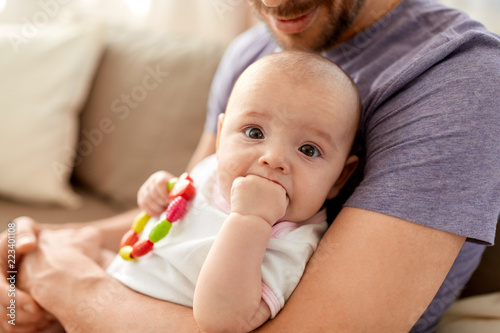 family, parenthood and people concept - close up of father with little baby girl at home - 223401108