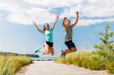 fitness, sport and lifestyle concept - happy couple in sports clothes jumping on beach - 223402907