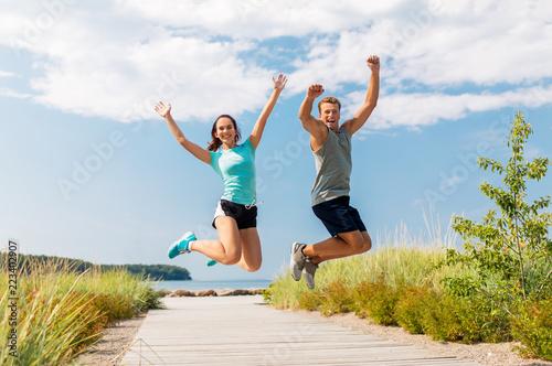 sprawności fizycznej, sporta i stylu życia pojęcie, - szczęśliwa para w sportach odziewa doskakiwanie na plaży