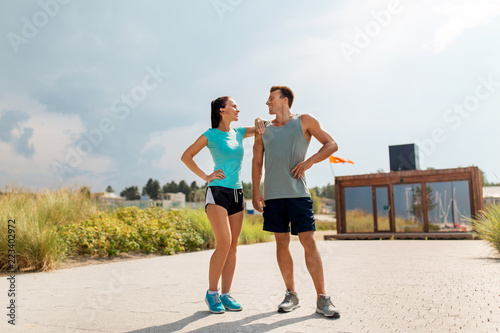 Foto Murales fitness, sport and lifestyle concept - happy couple in sports clothes outdoors