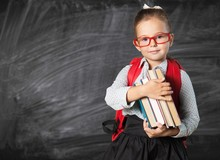 "Постер, картина, фотообои ""Cute little schoolgirl in glasses on blackboard"""