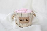 Set of pink towels in a wooden decorative bucket with the inscription