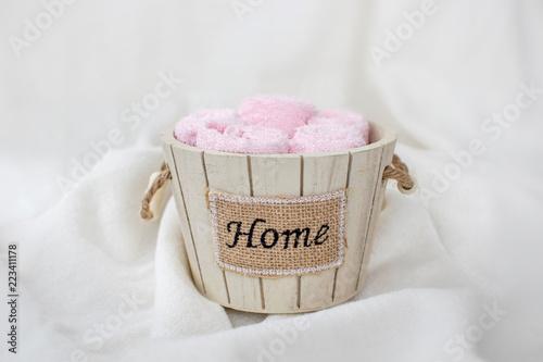 """Zestaw różowych ręczników w drewnianym ozdobnym wiaderku z napisem """"dom"""" na miękkim białym tle"""