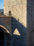 Steinerner Turm mit Brücke wirft Schatten auf Mauer, Massa Marittima, Italien - 223420178