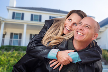 Happy Couple Hugging in Front of Beautiful House