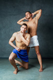 men with towels on their hips  against studio background - 223420700
