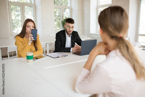 b7d0504f93c2 Young business man in eyeglasses with laptop talking to applicant while  business woman thoughtfully using cellphone