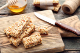 Tasty granola bars with knife on cutting board - 223424996