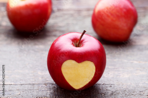 Red apple with cutout heart shape on grey wooden table