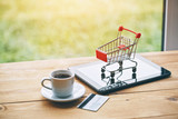 coffee cup and digital tablet with credit card and trolley as symbol of online shopping and paying