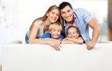 Beautiful smiling family sitting at sofa on background - 223438126
