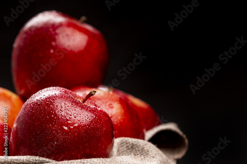 Bunch of wet red apples lying in braided bowl on black background © aitormmfoto