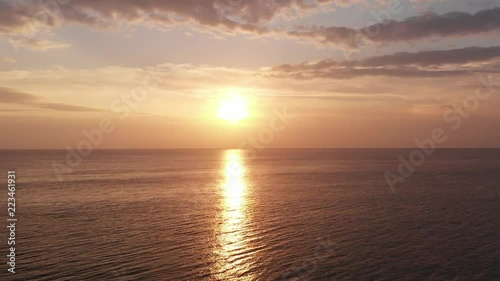 View from a Drone Flying up at Sunrise over the Sea