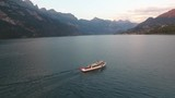 Chasing a ship with a drone on a lake in the swiss alps. - 223467114