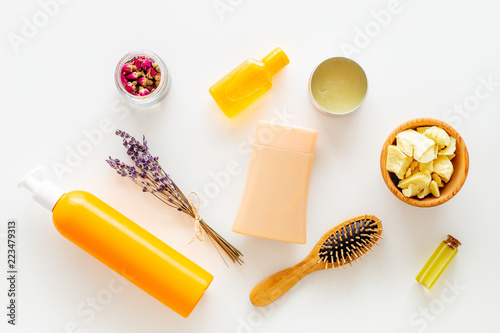 Cosmetics for hair care with jojoba, argan or coconut oil. Bottles and pieces of oil on white background top view