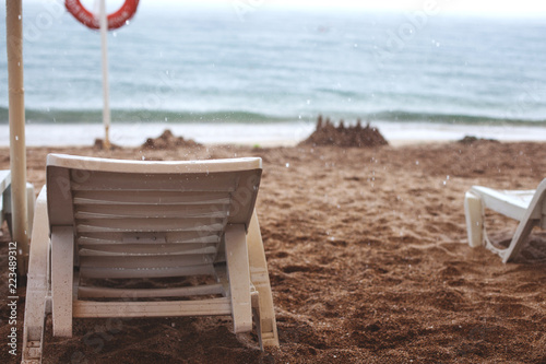rainy weather on the beach, chaise lounge on the beach - 223489312