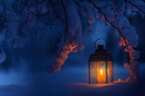 Candle lantern under the snowy branches at dusk. Christmas time in a wintery garden. - 223496176