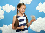 girl has a big dandelion in her hands, dressed in striped dress, posing on a blue background with cotton clouds, the concept of summer, holiday and happiness