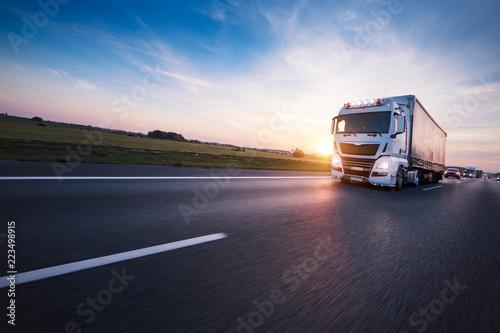 Loaded European truck on motorway in sunset - 223498915
