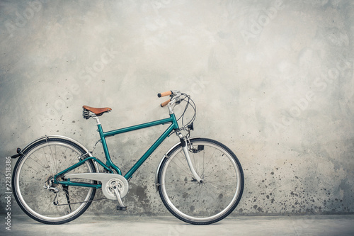 Leinwandbild Motiv Retro bicycle with aged brown leather saddle from circa 90s front concrete wall background. Vintage old style filtered photo