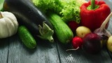 Composition of multicolored vegetables in assortment in water drops lying on gray wooden table in daylight - 223521982