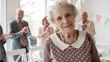 Portrait of happy senior woman smiling and posing for camera in the living room while joyous friends standing in background and clapping hands at birthday party - 223522394