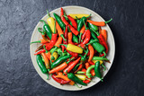 Different colors hot peppers in wooden plate closeup. Food photography - 223532924