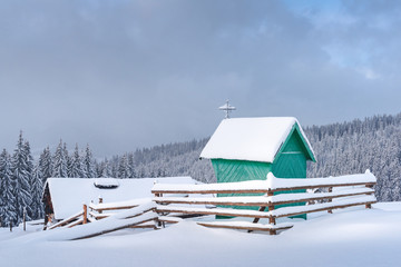 Fantastic winter landscape with green wooden chapel and house in snowy mountains. Christmas holiday concept. Carpathians mountain, Ukraine, Europe