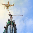 Leinwanddruck Bild - Drone over construction site of modern office and residential building in Singapore. Concept of video surveillance or industrial safety inspection