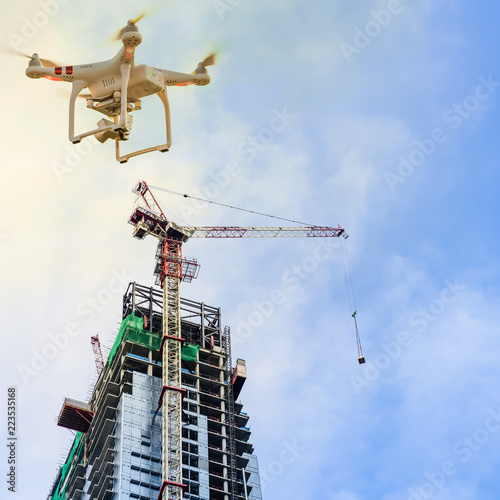 Leinwanddruck Bild Drone over construction site of modern office and residential building in Singapore. Concept of video surveillance or industrial safety inspection