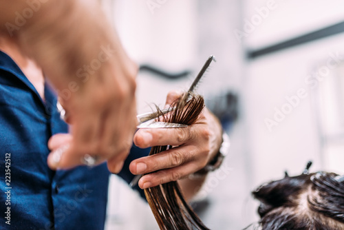 Professional male hairdresser cutting female customers hair. Close-up.