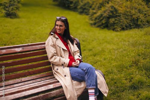 Portret kobiety w pełnej długości sobie beżowy trencz, czerwona Bluza z kapturem, niebieskie dżinsy podczas spaceru w parku i siedząc na ławce.