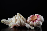 Two heads of fresh garlic on a black background. - 223546580