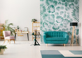White living room interior with leafy wallpaper in the real photo with turquoise sofa, fresh plants, wooden desk and empty wall with place for your poster - 223558377