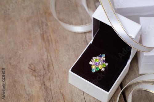 Srebrny pierścionek z kolorowymi klejnotami w białym pudełku