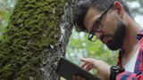 Modern male hipster with a tablet in the forest is studying trees. Ecologist studies moss on a tree and writes data to a tablet computer. Botanist in glasses and with a tablet is engaged in research. - 223571543