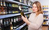 Female buying bottle of wine - 223573789