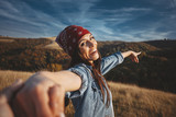 Happy young woman holds the hand of a man in nature - 223590700