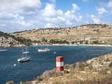 Karge Bucht mit blauem Wasser vor weiss blauem Himmel mit rotem Holzpfahl im Vordergrund, Malta - 223593339