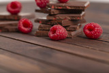 A stack of chocolate bars with built-in red raspberry berries. Fresh raspberries and chocolate on wooden background.