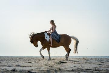 Mädchen auf bockendem Pferd am Strand © Nadine Haase