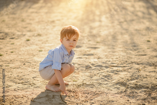 Foto Murales Three year old toddler boy playing on beach. Rest on summer vacation