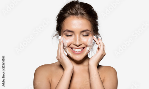 Leinwandbild Motiv Portrait of cheerful laughing woman applying foam for washing on her face. Lovely brunette with attractive appearance. Skincare spa relax concept. Isolated on grey background