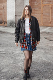 Portrait of a woman in rock, grunge style. Filmed on the street, in the open space. Dressed in a black leather jacket, shirt in red plaid. Street style and fashion. - 223618556