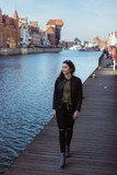 Young woman with dark hair walking along the river in old town of Gdansk, Poland